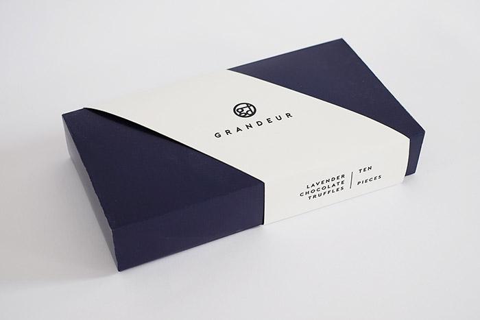 富丽堂皇是一种以澳大利亚为基础的巧克力块菌标签。他们的产品提供高端豪华包装和豪华巧克力松露。 主要项目是为巧克力块菌制作一个豪华的包装设计,并为该品牌设计一个标识。我们需要考虑的不是仅仅让它看起来很好,而是考虑它是否适用于巧克力包装。设计理念是将极简主义与高标准的豪华包装结合起来。 身份的设计是一个字母和类型的组合。该标志的方向是极简主义,混合优雅。至于包装,方向也是优雅的。选择的颜色是皇家蓝与白色肚皮带混合。至于巧克力保持架,则采用黑色专用纸增强整体包装,外观豪华。  高端豪华巧克力松露礼盒包装设计、巧
